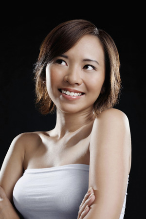 tube top: Woman in white tube top smiling with arms folded