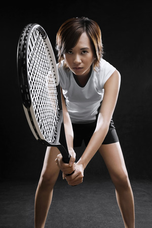 tennis racquet: Woman holding tennis racquet, preparing to hit