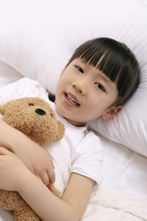 soft toy: Girl lying on bed hugging soft toy