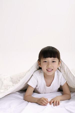 lying forward: Girl lying forward with blanket over her head LANG_EVOIMAGES