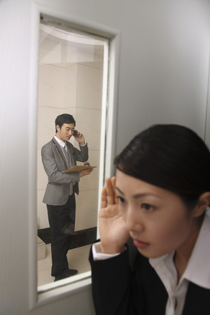eavesdropping: Businesswoman eavesdropping on businessman talking on the phone LANG_EVOIMAGES