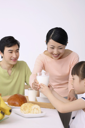Woman giving girl a glass of milk, man watching