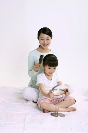 Woman combing girls hair