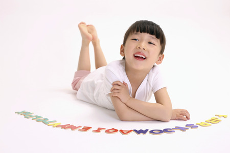 lying forward: Girl lying forward on floor with alphabets arranged at her side LANG_EVOIMAGES