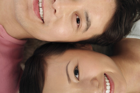 Man and woman lying down on carpet smiling