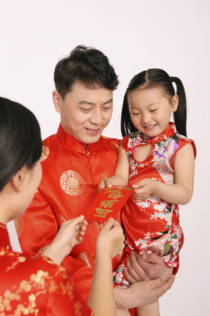 red packet: Woman giving red packet to girl, man watching