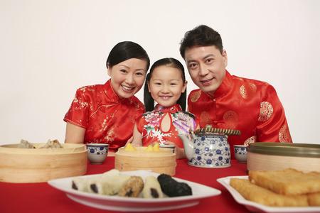 Glückliche Familie in traditioneller chinesischer Kleidung lächelnd LANG_EVOIMAGES