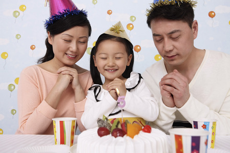 family: Man, woman and girl making a wish in front of birthday cake