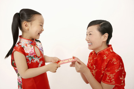 red packet: Woman giving girl red packet LANG_EVOIMAGES