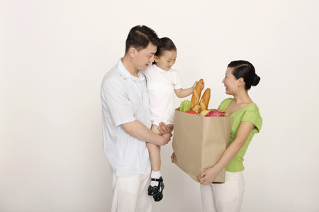 carrying girl: Woman holding a bag of groceries, man carrying girl LANG_EVOIMAGES