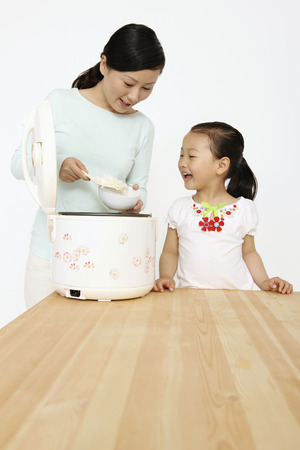 rice cooker: Woman scooping rice from rice cooker while girl looks on