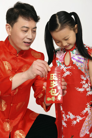 into: Man and girl looking into red packet, smiling