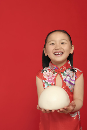 widely: Girl holding big chinese steamed bun, smiling widely LANG_EVOIMAGES