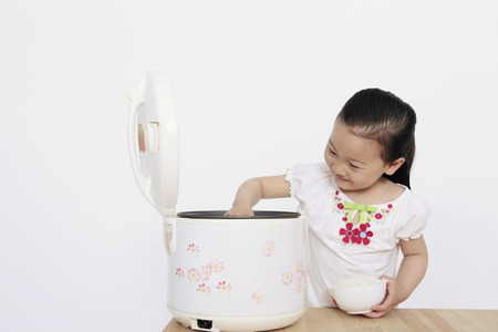 rice cooker: Girl scooping rice from rice cooker LANG_EVOIMAGES
