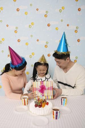 cadeau anniversaire: Fille d'ouvrir son cadeau d'anniversaire avec l'homme et la femme