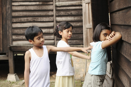 malay village: Children playing traditional game in the house compound LANG_EVOIMAGES