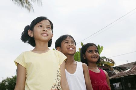 malay village: Los ni�os de pie en una fila y mirando a otro lado