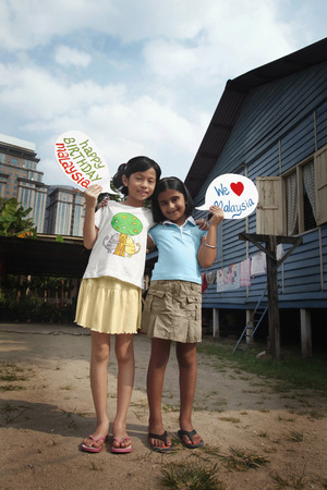 placards: Children holding placards displaying We love Malaysia and Happy Birthday Malaysia LANG_EVOIMAGES