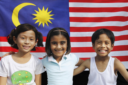 Children sitting in front of Malaysian flag