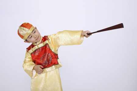 traditional costume: Boy in traditional costume holding hand-held fan
