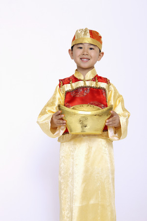 gold ingot: Boy in traditional costume holding a gold ingot LANG_EVOIMAGES