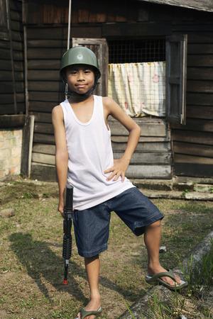 malay village: Muchacho con el sombrero soldado sosteniendo rifle de juguete
