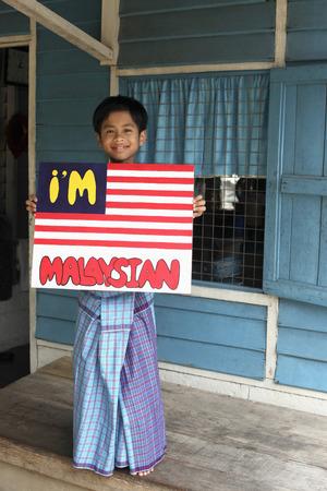malay village: Ni�o de pie en el porche que sostiene un cartel LANG_EVOIMAGES