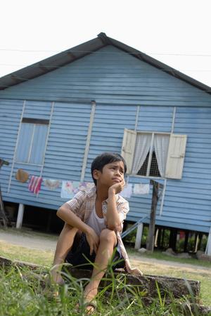 malay village: Ni�o sentado en la roca, contemplando