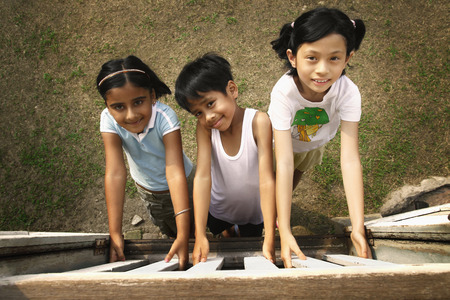 three people only: Children holding onto wooden house window from outside