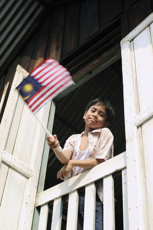malay village: Boy waving flag from an opened window