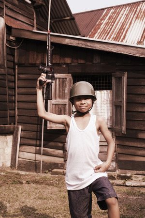malay village: Boy with soldier hat holding toy rifle