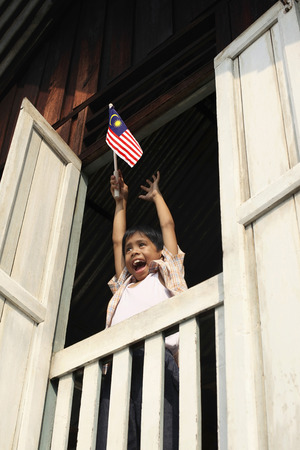 malay village: Boy raising hands while holding flag