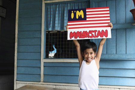 merdeka: Boy holding up a poster