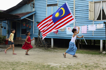 Boy running with flag in hands, girls running behind him LANG_EVOIMAGES