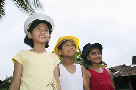 only three people: Children in different uniform hats