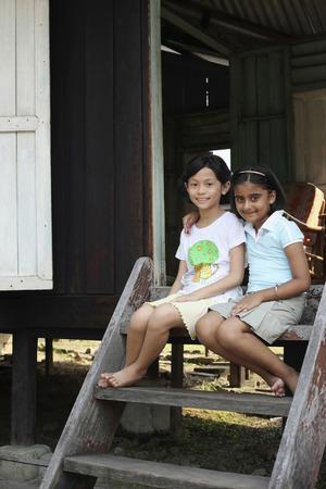 malay village: Muchachas que se sientan en las escaleras LANG_EVOIMAGES