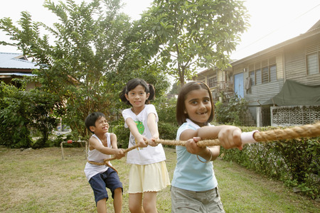 only three people: Children playing tug-of-war