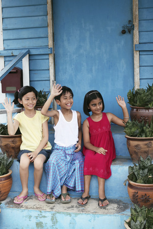 only three people: Children waving while sitting on stairs