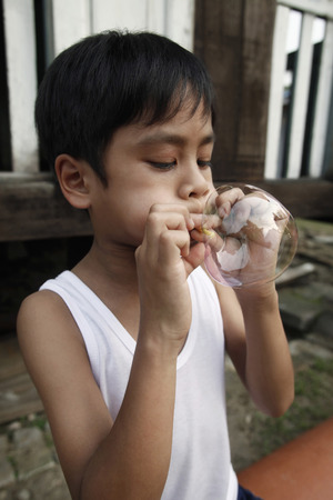 elementary age boys: Boy blowing bubble LANG_EVOIMAGES