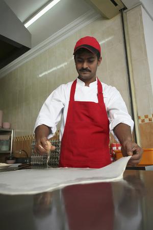 breaking: Man breaking egg onto flattened dough