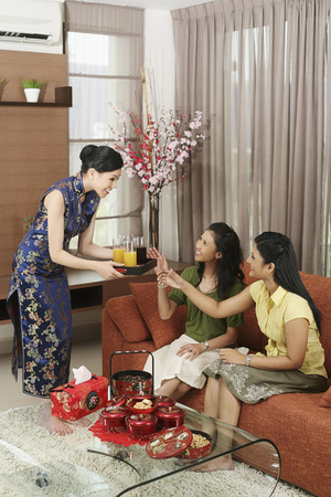three people only: Woman serving her friends drinks during Chinese New Year open house LANG_EVOIMAGES