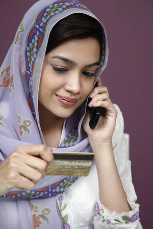 traditional clothing: Businesswoman in traditional clothing referring to credit card while talking on the phone LANG_EVOIMAGES