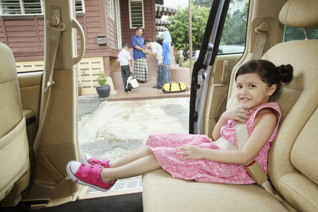 family bonding: Girl waiting in the car, man greeting senior man in the background LANG_EVOIMAGES