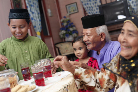 Älterer Mann und Frau Cookies mit ihren Enkelkindern genießen