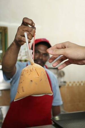 tarik: Man giving iced teh tarik to customer LANG_EVOIMAGES