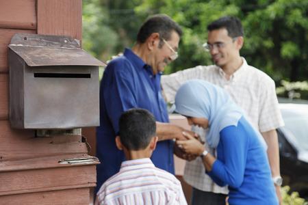 malay village: Woman greeting senior man, man and boy watching LANG_EVOIMAGES