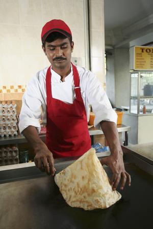 shaping: Man shaping roti tisu