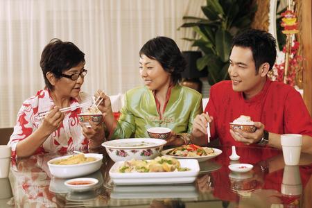 Woman taking food for senior woman, man watching Stock Photo - 39014116