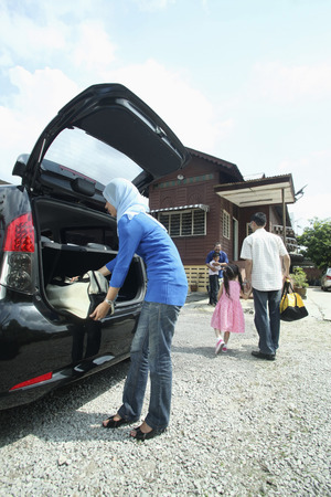 Woman keeping luggage in the car trunk, boy hugging senior man in the background