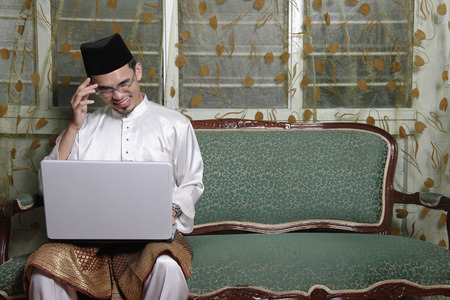 traditional clothing: Man in traditional clothing using laptop